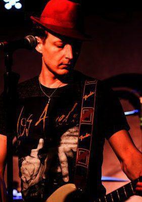 CMS Dozent Franz Schedlbauer trägt einen Hut und gibt E-Gitarrenunterricht in Bergedorf