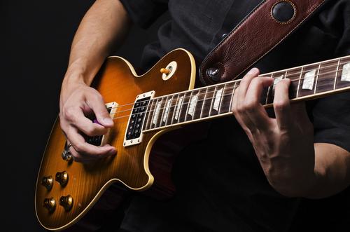Mann während des E-Gitarrenunterrichts