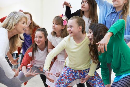 Kinder spielen und machen zusammen mit einer Frau, die offensichtlich ihre Musiklehrerin ist, Grimassen
